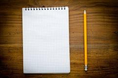 Svart anteckningsbok med pencile på en wood bakgrund Arkivbild