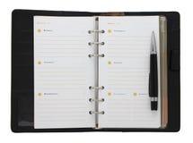 Svart anteckningsbok och en penna Arkivbilder
