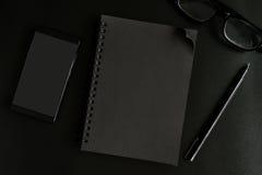 Svart anteckningsbok och mobiltelefon på skrivbordkontor Arkivbilder