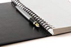 Svart anteckningsbok på en vit bakgrund Arkivfoto