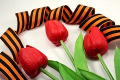 Svart-apelsin band med tre blommor av en tulpan Royaltyfri Foto