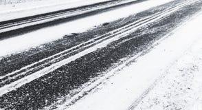 Svart asfalttrottoar under det nya snölagret Royaltyfri Foto