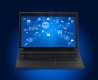Svart bärbar dator med datorsymboler på blått Arkivbild
