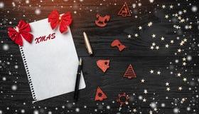 Svart bakgrund av Xmas claus bokstav santa toys trä Röda pilbågar Utrymme för text Top beskådar Snö och ljus effekt royaltyfria bilder