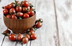 Svart bakgrund för körsbärsröd tomat Royaltyfri Foto