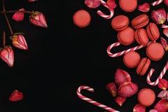 Svart bakgrund med kronblad av röda rosor, makron och karamellpinnar Royaltyfri Bild