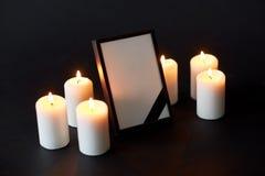 Svart band på fotoram och stearinljus på begravningen Royaltyfria Bilder