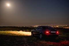 Svart bil i fältet på natten royaltyfri foto