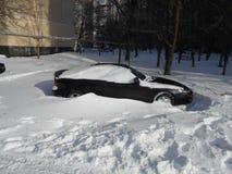 Svart bil i snödriva Arkivfoto