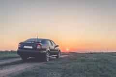 Svart bil på vägen på solnedgången arkivfoton