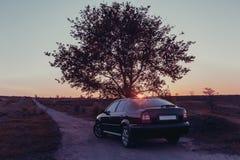Svart bil på vägen på solnedgången royaltyfria foton