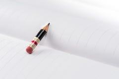Svart blyertspenna med det rosa radergummit på ett papper Arkivbild