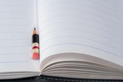 Svart blyertspenna med det rosa radergummit på ett papper Arkivfoto