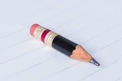 Svart blyertspenna med det rosa radergummit på ett papper Arkivfoton