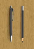 Svart blyertspenna och penna på trätabellen Royaltyfri Bild