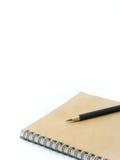 Svart blyertspenna på en brun anteckningsbok i vit bakgrund Arkivbilder
