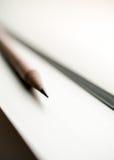 Svart blyertspenna på vit bakgrund i morgonljus Arkivbild