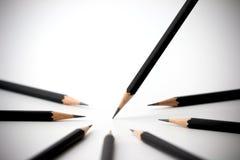 Svart blyertspenna som står ut från folkmassan av identiska svarta kamrater för överflöd affärsidé isolerad framgångswhite Fotografering för Bildbyråer