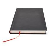 Svart bok med en röd bokmärke Arkivfoto
