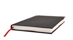 Svart bok med en röd bokmärke Arkivbild