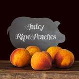 Svart brädesvin som annonserar nya mogna organiska persikor Royaltyfria Bilder