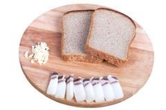 Svart bröd, bacon, vitlök på ett bräde som isoleras på den vita backgrouen Royaltyfri Bild