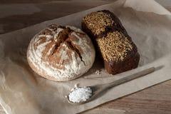 Svart bröd för runda och för råg med sesam och en sked av salt på papper Fotografering för Bildbyråer