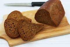 Svart bröd för smörgåsar klipps in i skivor på ett träbräde på en vit bakgrund royaltyfria bilder