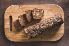 Svart bröd på en skärbräda arkivfoto