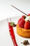 Svart breton eller Bretonmördegskaka med vaniljkräm- och halloncoulis på den vita maträtten Royaltyfri Bild