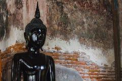 Svart Buddha bredvid gamla väggar i thailändska tempel arkivfoto