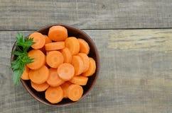 Svart bunke med klippta morötter som är färdiga på träbakgrund Royaltyfri Fotografi