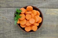 Svart bunke med klippta morötter som är färdiga på träbakgrund Arkivfoto