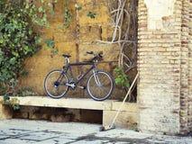 Svart cykel som parkeras på stenväggen Arkivfoton