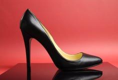 Svart den kvinnliga stilettkickhälet skor på röd bakgrund Arkivfoton