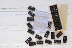 Svart domino och anvisning på den vita trätappningtabellen royaltyfri foto