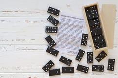 Svart domino och anvisning på den vita trätappningtabellen fotografering för bildbyråer