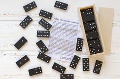 Svart domino och anvisning på den vita trätappningtabellen arkivfoton