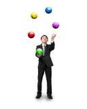 Svart dräktaffärsman som jonglerar bollar för valutasymbol Arkivbild
