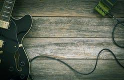 Svart elektrisk gitarr, effektpedal på ett lantligt trä arkivbild
