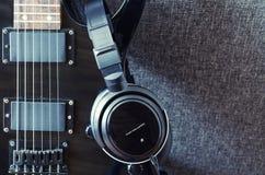 Svart elektrisk gitarr och hörlurar royaltyfri bild