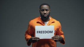 Svart fängslade det manliga hållande frihetstecknet i cellen som frågar för hjälpmänskliga rättigheter stock video