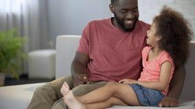 Svart fader och dotter som skrattar och att spendera tid tillsammans, vänlig familj arkivfoto