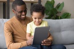 Svart fader som undervisar liten sonbruksminnestavla den elektroniska apparaten royaltyfria bilder