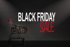 SVART FIDAY SALE med shoppingvagnen på en svart bakgrund arkivbilder
