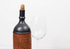 Svart flaska av vin och wneglass på träbakgrunden Royaltyfri Foto
