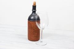 Svart flaska av vin och wneglass på träbakgrunden Arkivfoto