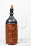 Svart flaska av vin och wneglass på träbakgrunden Fotografering för Bildbyråer