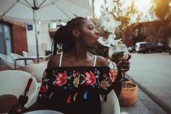 Svart flicka med kalebassen och coctail i kafé utomhus arkivfoto