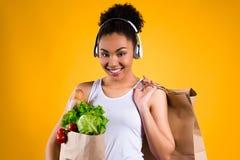 Svart flicka med livsmedel i isolerad hörlurar royaltyfria foton